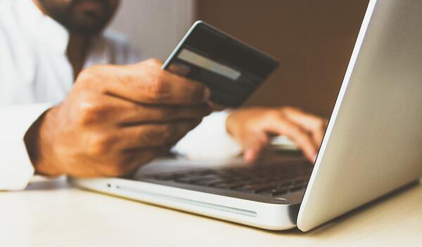 Man with laptop and credit card out to make purchase
